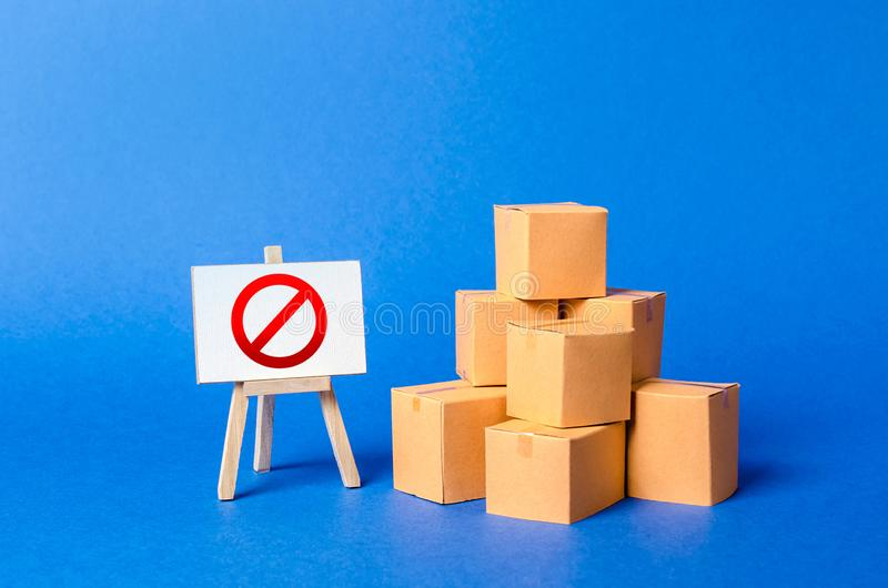 Caixas de cartão da pilha da pilha e um suporte do sinal com símbolo vermelho NÃO Limitação na importação de bens, proprietária foto de stock royalty free