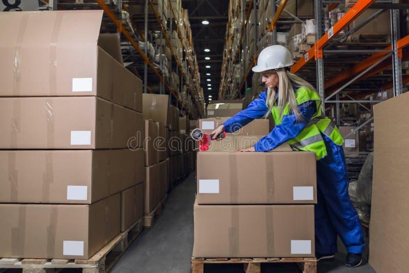 Caixas de embalagem do trabalhador do armazém no depósito fotografia de stock