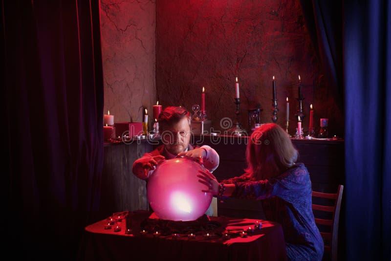 Caixas de fortuna do homem e da mulher com bola de cristal imagem de stock royalty free
