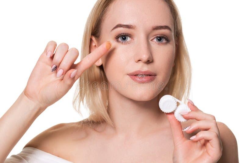 Caixas de lentes do contato da terra arrendada da jovem mulher e lente na frente de sua cara no fundo branco foto de stock