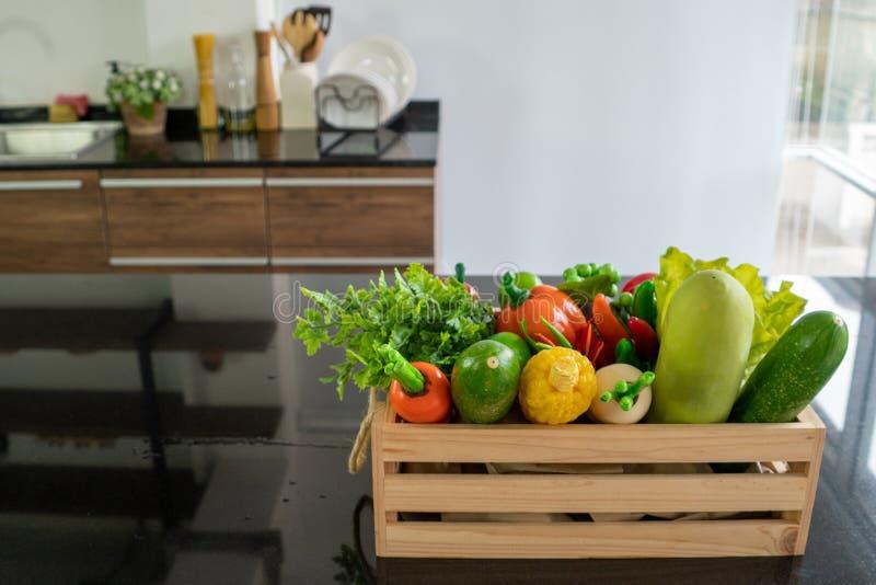 Caixas de madeira enchidas com os vários tipos dos legumes frescos colocados no contador na cozinha fotos de stock