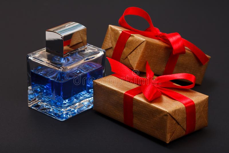 Caixas de presente amarradas com fita e a garrafa vermelhas do perfume no fundo preto fotos de stock