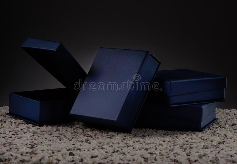 Caixas de presente azuis em seixos do mar e no fundo cinzento foto de stock