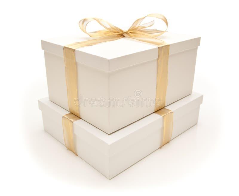 Caixas de presente brancas empilhadas com a fita do ouro isolada fotografia de stock