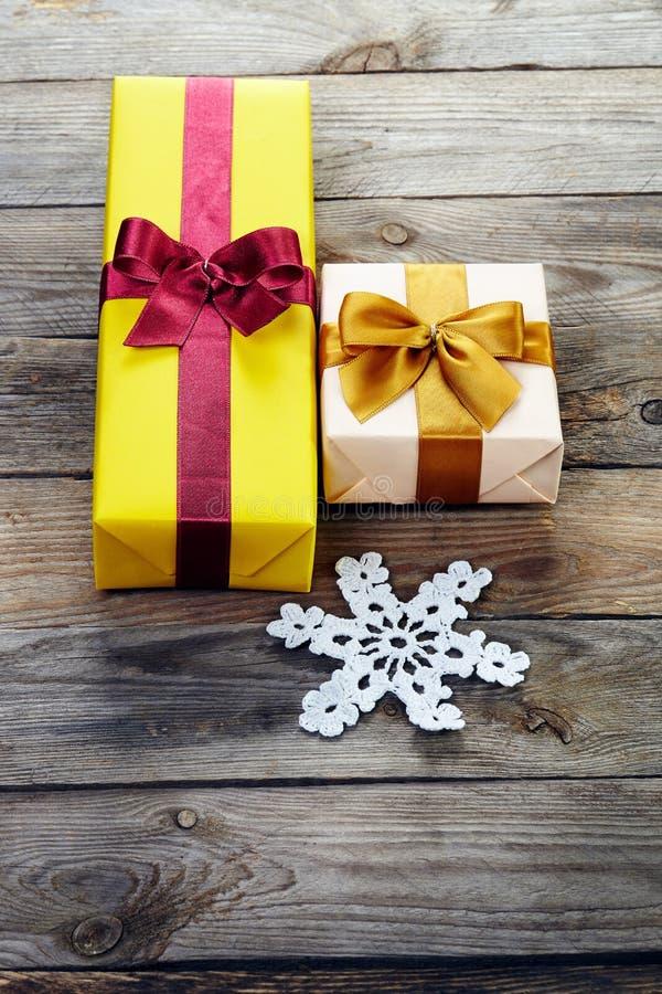 Caixas de presente coloridas com curvas e flocos de neve sobre o backgr de madeira imagem de stock royalty free