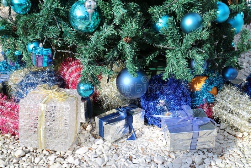 Caixas de presente coloridas do Natal sob a árvore de Natal decorada com quinquilharias e ouropel fotografia de stock