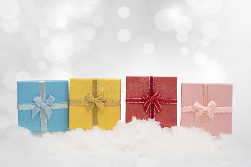 Caixas de presente coloridas na queda de neve com espaço da cópia para a estação g imagem de stock