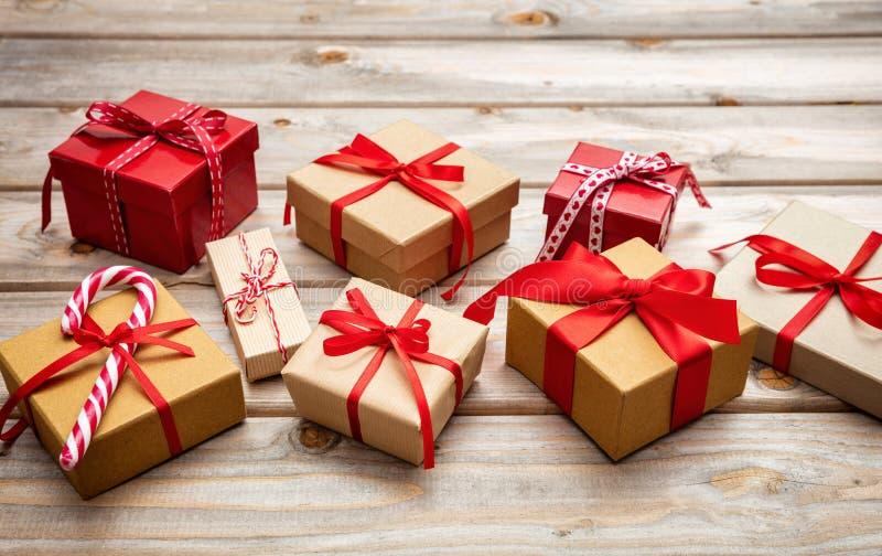 Caixas de presente com as fitas vermelhas no fundo de madeira, espaço da cópia imagem de stock royalty free