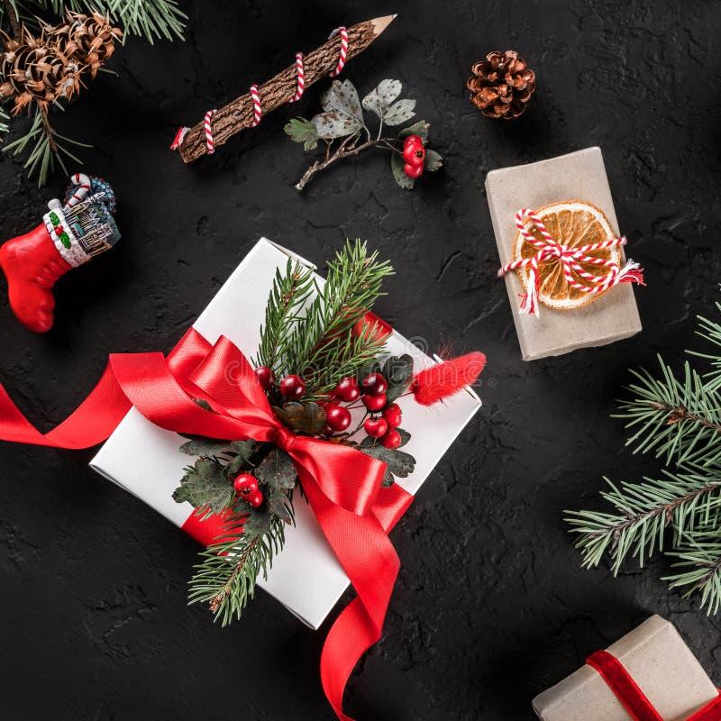 Caixas de presente com a fita vermelha no fundo do feriado com lápis, ramos do Natal do abeto, cones do pinho Cartão do Xmas e do fotografia de stock