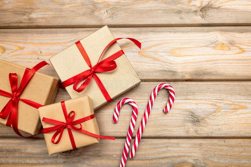 Caixas de presente com os bastões vermelhos da fita e de doces no fundo de madeira, espaço da cópia, vista superior imagem de stock