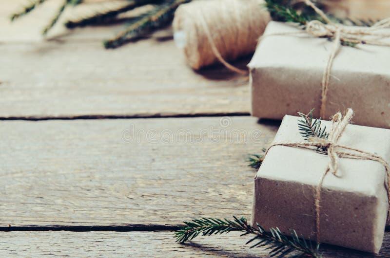 Caixas de presente com ramos do abeto em um fundo de madeira Estilo rústico Preparação do conceito pelo ano novo Copie o espaço imagens de stock