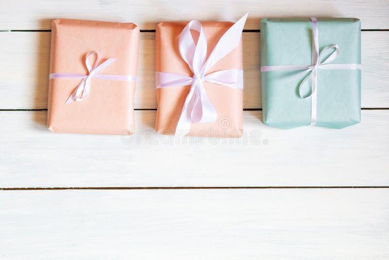 Caixas de presente das cores do pêssego e da hortelã no fundo de madeira branco Luz natural Lugar livre para sua configuração lis fotografia de stock