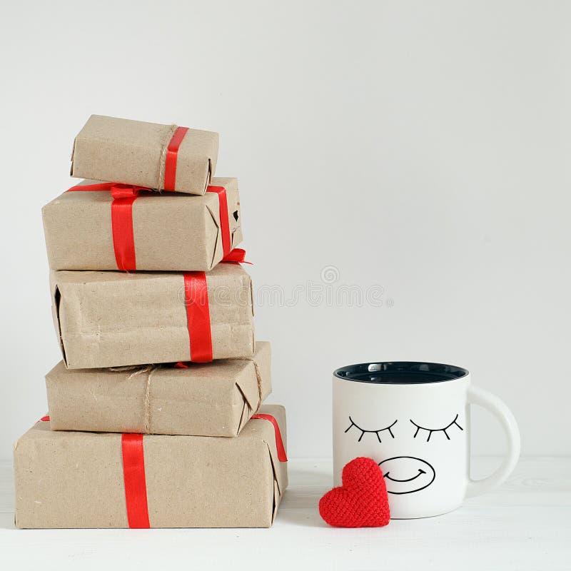 Caixas de presente do dia de Valentim, coração do brinquedo e copo de café com os olhos engraçados os mais bonitos no fundo branc imagens de stock royalty free