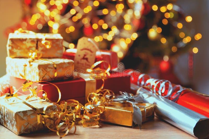 Caixas de presente do Natal com fitas e papel de envolvimento contra o bokeh do fundo de luzes do partido e da árvore de abeto de imagem de stock