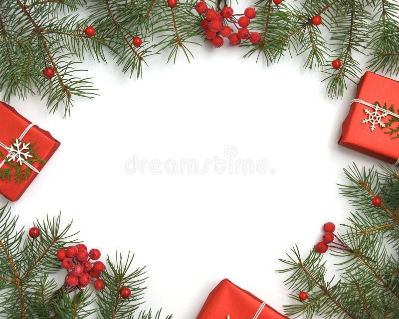 Caixas de presente do Natal decoradas com papel do ofício e os flocos de neve brancos na opinião superior do fundo vermelho Cartã imagens de stock