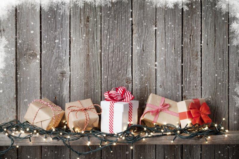Caixas de presente do Natal e luzes na frente da parede de madeira imagens de stock