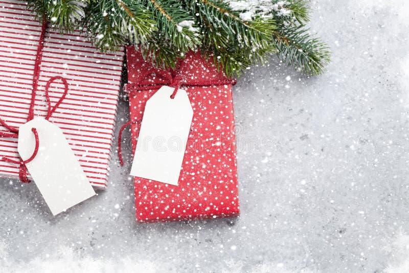 Caixas de presente do Natal e ramo de árvore do abeto coberto pela neve no fundo de pedra Contexto do xmas da vista superior com  imagem de stock royalty free