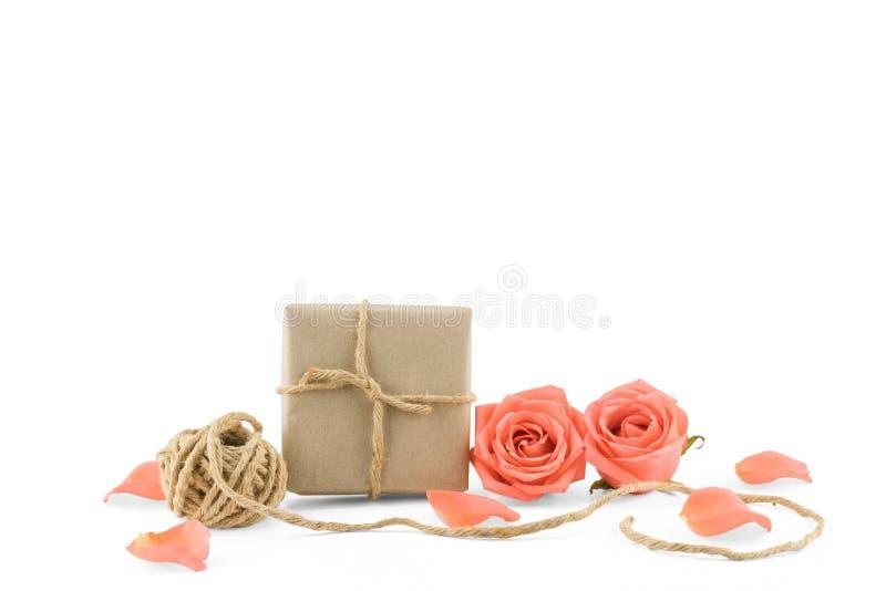Caixas de presente e corda de Brown com rosas e as pétalas alaranjadas imagens de stock royalty free