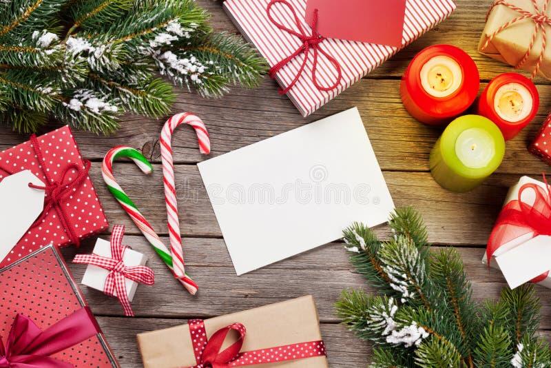 Caixas de presente e velas do Natal na tabela de madeira foto de stock