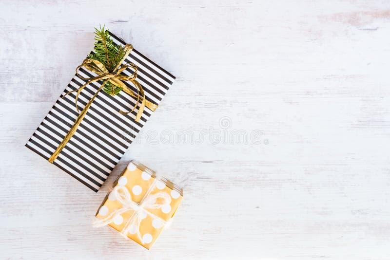 Caixas de presente envolvidas no papel pontilhado listrado e dourado preto e branco em um fundo de madeira branco Weihnachtspaket fotografia de stock royalty free
