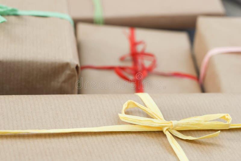 Caixas de presente envolvidas no papel reciclado com curvas da cor para Christm fotografia de stock royalty free