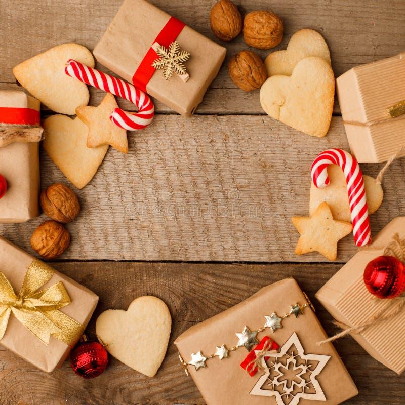 Caixas de presente feitos a mão, bastões de doces, noz e cookies do pão-de-espécie no fundo de madeira rústico, vista superior, e fotografia de stock