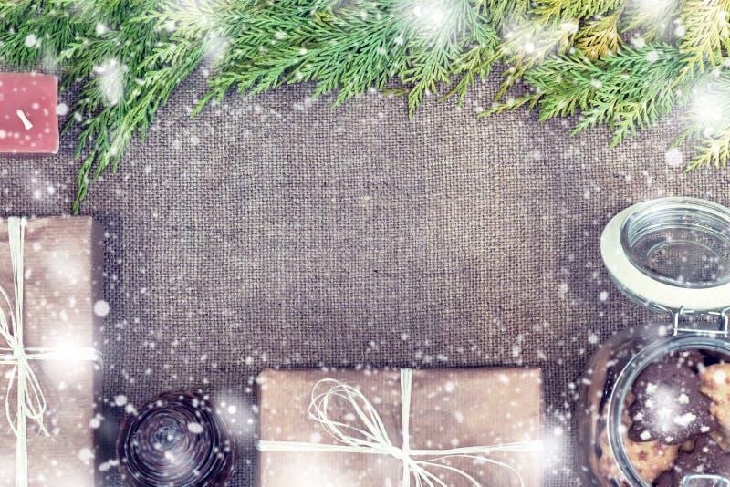 Caixas de presente feitos a mão do Natal decoradas com papel, ramo e floco de neve do ofício na opinião superior do fundo do pano imagem de stock royalty free