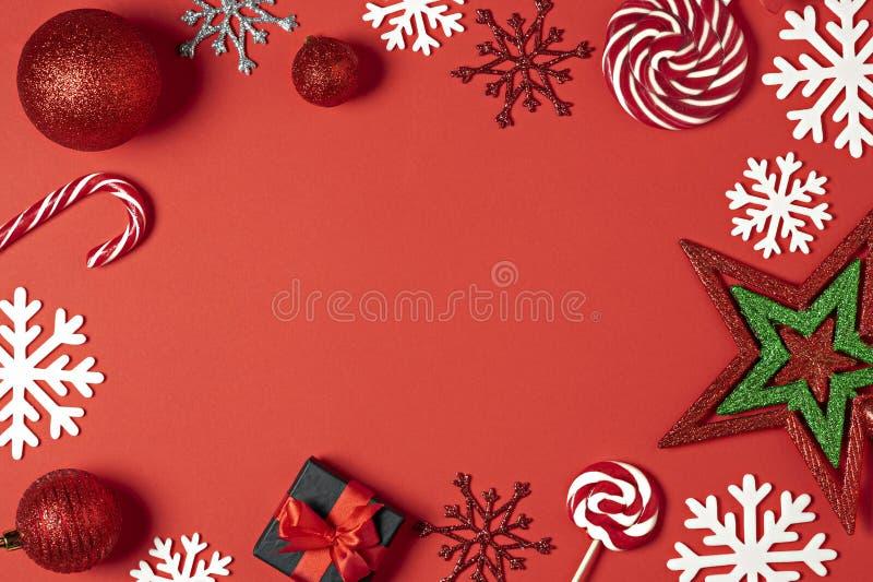 Caixas de presente feitos a mão do Natal decoradas com papel vermelho, doces, estrela, flocos de neve brancos na opinião superior fotos de stock royalty free