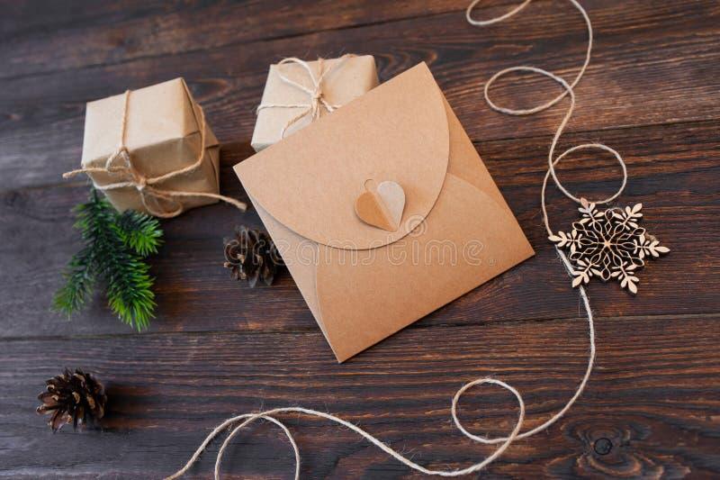 Caixas de presente de kraft do Natal do modelo com os brinquedos de madeira do xmas no fundo de madeira Vista superior para o car fotografia de stock