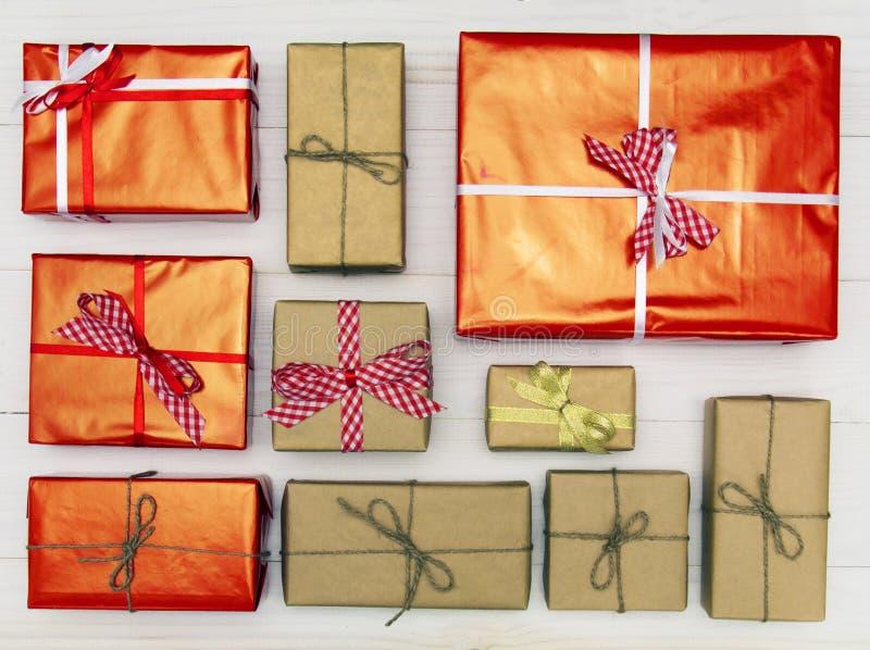 Caixas de presente na opinião superior do fundo de madeira branco Muitos presentes e surpresas dos presentes para o Natal, feriad imagens de stock