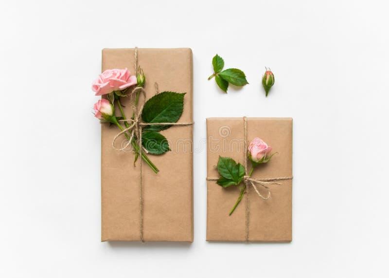 Caixas de presente no papel do eco no fundo branco Presentes decorados com rosas Conceito do feriado, vista superior, configuraçã imagens de stock royalty free