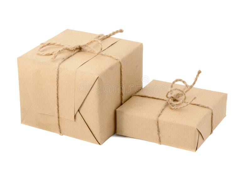 Caixas de presente ou pacotes do correio, envolvidos com o papel de embalagem e a guita isolados imagem de stock