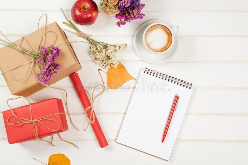 caixas de presente outono-temáticos do artesanato, folhas amarelas decoradas, flores Um copo do cappuccino e caderno com lápis foto de stock royalty free
