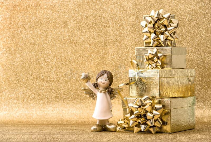 Caixas de presente pouca decoração dourada do Natal do fundo do anjo imagem de stock