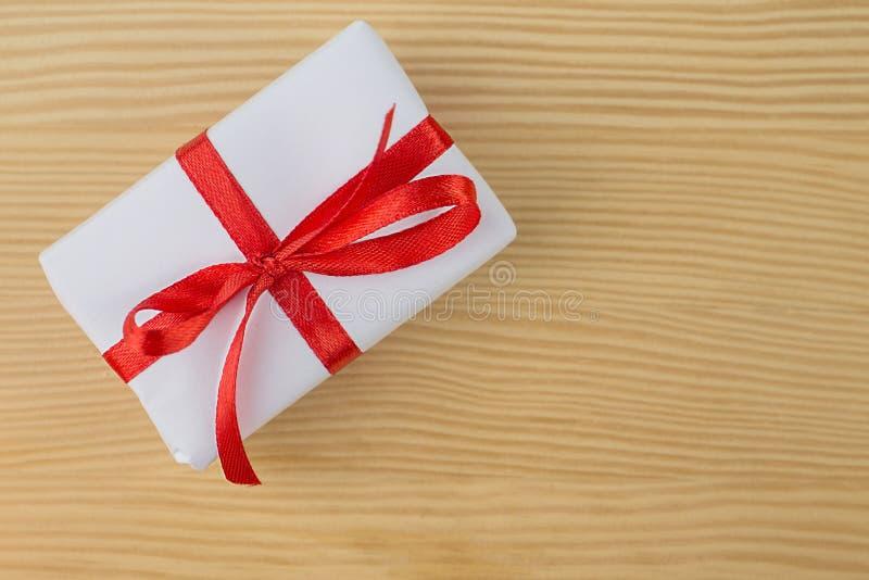 Caixas de presente vermelhas e brancas com curvas e fitas em um fundo de madeira natural foto de stock royalty free