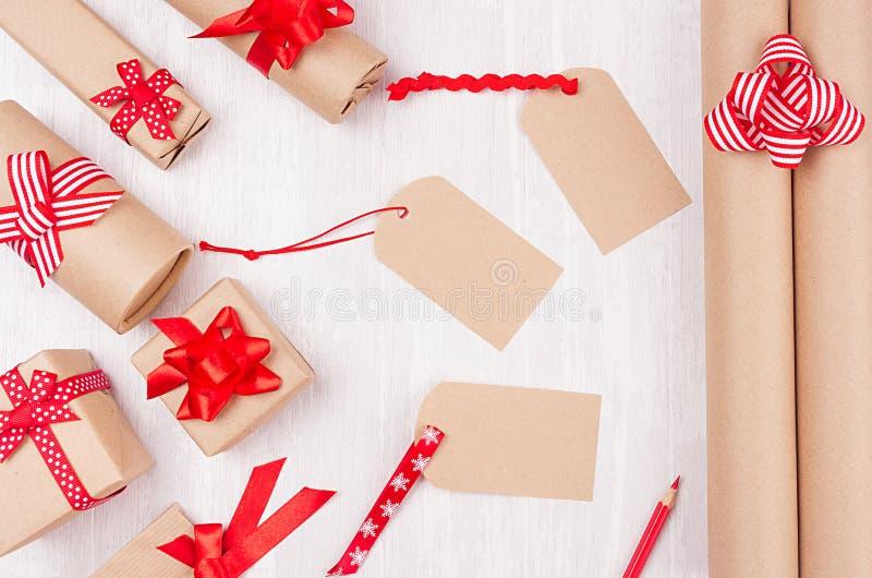 Caixas de presentes do Natal do papel de embalagem com curvas e a fita vermelhas e de etiquetas vazias na placa de madeira branca imagem de stock royalty free
