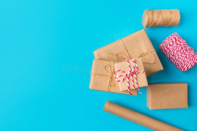 Caixas de presentes rolam de fita branca vermelha-marrom-Kraft sobre fundo azul O Natal de Ano Novo apresenta as compras imagem de stock