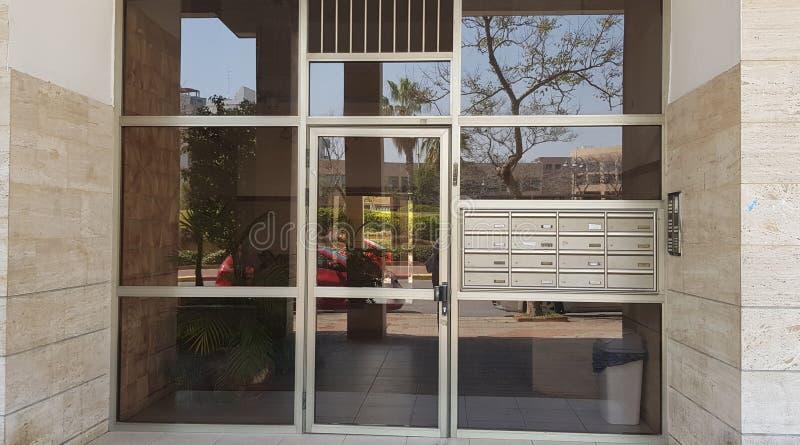 Caixas de vidro da porta e do correio na entrada à construção compartilhada fotos de stock