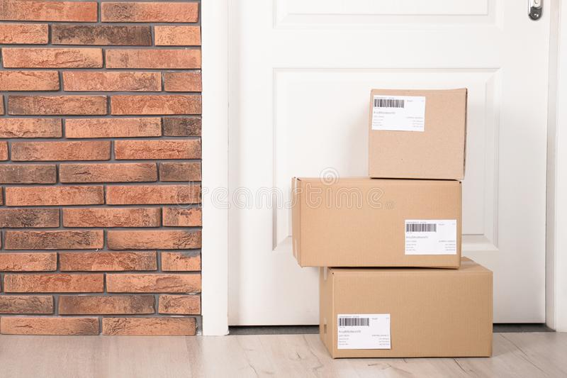 Caixas do pacote do cartão no assoalho perto da entrada Modelo para o projeto imagem de stock