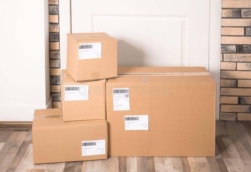 Caixas do pacote do cartão no assoalho perto do entrancem do apartamento fotografia de stock royalty free