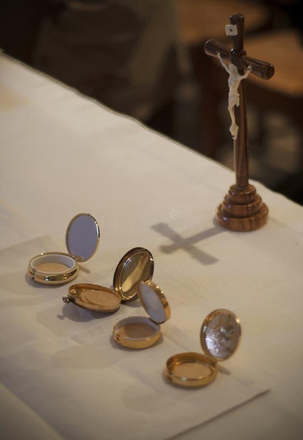 Caixas douradas e cruz das bolachas santamente em um altar em uma igreja Católica francesa imagem de stock