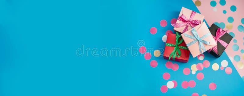 Caixas e confetes decorados no fundo cor-de-rosa e azul fotografia de stock