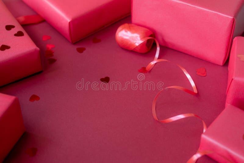Caixas, fita e confetes vermelhos diferentes no fundo vermelho Conceito para o dia de Valentine's foto de stock