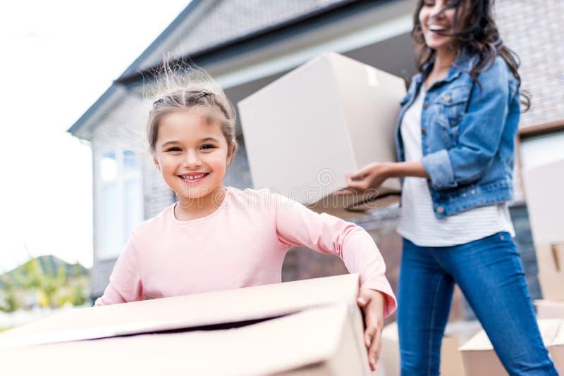 caixas levando da mãe e da filha para mover-se em imagens de stock