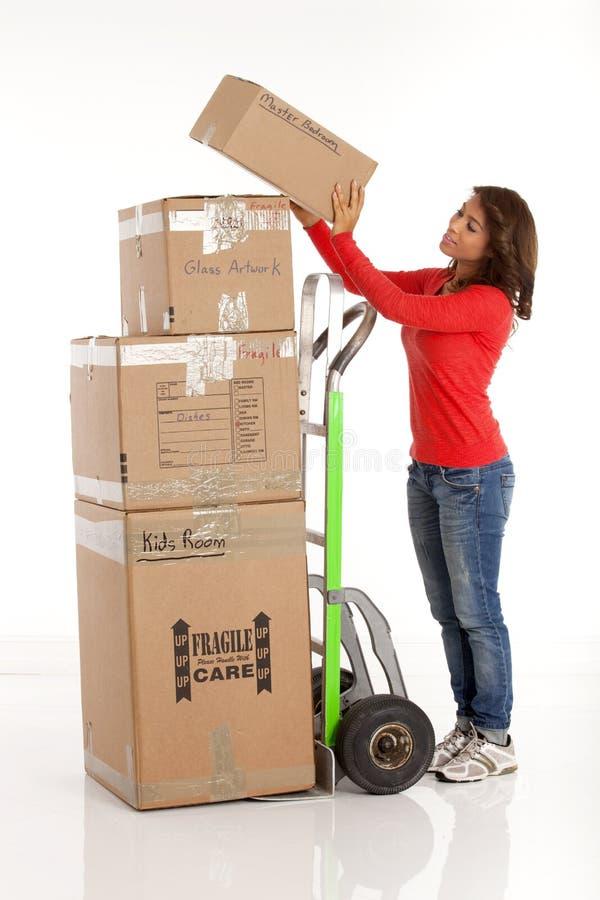 Caixas moventes da jovem mulher com com um caminhão ou uma zorra de mão fotografia de stock royalty free