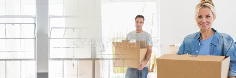 Caixas moventes dos pares felizes em sua casa nova foto de stock