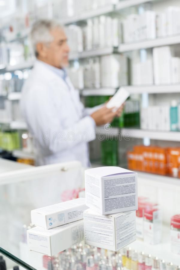 Caixas no contador com químico Working In Pharmacy foto de stock