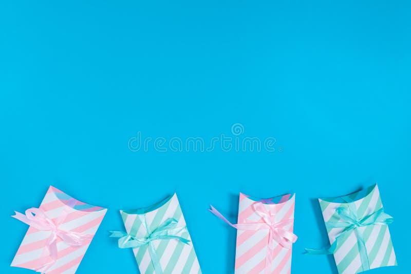 caixas-presentes cor-de-rosa e verde-claro colocadas sobre um fundo azul localizado na parte inferior da imagem foto de stock royalty free