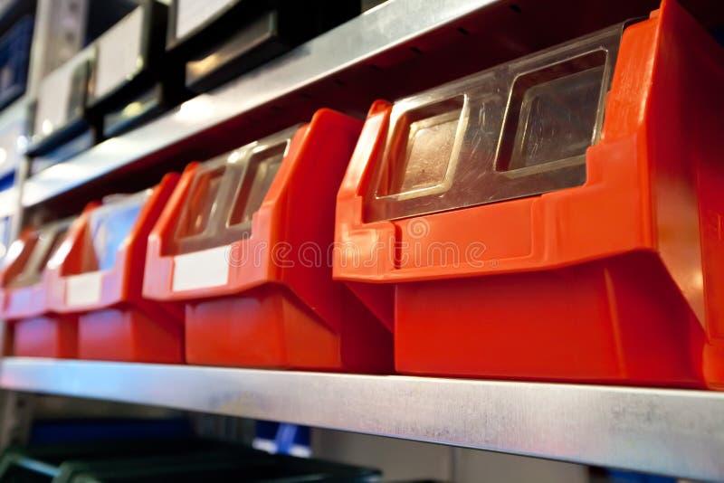 Caixas vermelhas no escaninho conservado em estoque em um armazém imagem de stock royalty free