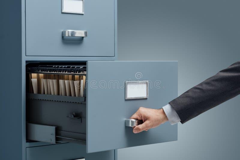 Caixeiro de escritório que procura arquivos em um arquivo imagens de stock royalty free